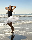 Young woman twilring skirt in waves. Young woman on beach twirling Royalty Free Stock Photo