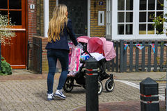 Young woman with twins pram walking along a street in Zandvoort, Stock Photography