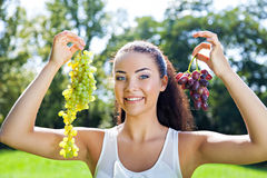 Young woman with two bunches of grapes Royalty Free Stock Images