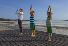 Young woman and two children  practicing yoga on the beach. Royalty Free Stock Photography
