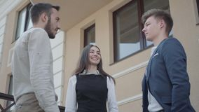Young woman and two cute men in formal wear high five together on the terrace. Business relationship. Concept of. A young woman and two men in formal wear high stock video