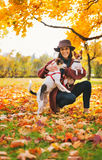 Young woman with two dogs playing outside in autumn leaves Royalty Free Stock Images