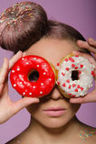 Young woman with two donuts before eyes Royalty Free Stock Photos