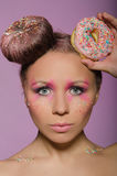 Young woman with two donuts on head Royalty Free Stock Image