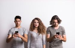 A young woman with two friends occupied with modern technology. A sad young women with twp male friends occupied with modern technology, a stand from the crowd royalty free stock images