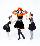 Young woman and two girls in cat carnival costumes posing Stock Image