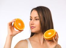Young woman and two halves of orange Stock Images