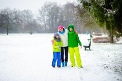 Young woman and two of her sons cheerfully spend time in the park in winter day. Royalty Free Stock Image