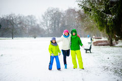 Young woman and two of her sons cheerfully spend time in the park in winter day. Royalty Free Stock Photos