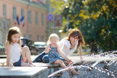 Young woman and two kids by a city fountain Royalty Free Stock Photography