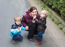 Young woman and two little boys eating ice cream Stock Image