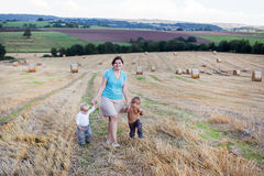 Young woman and two little boys walking through hay field Royalty Free Stock Photo