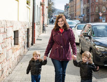 Young woman and two little boys walking through spring city Royalty Free Stock Images