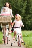 Young woman with two little girls riding bicycles in park. Portrait of young women with two little girls riding bicycles in park stock images