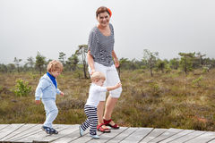 Young woman and two little toddler boys in nature park Royalty Free Stock Photo