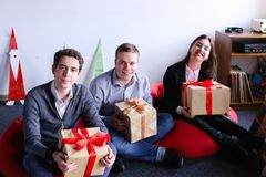 Young woman and two man posing and smiling with holiday boxes wi royalty free stock image