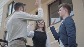 Young woman and two men in formal wear high five together on the terrace. Business relationship. Concept of freelance. A young woman and two men in formal wear stock footage