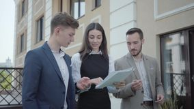 Portrait young woman and two men in formal wear walking on terrace discussing project. Concept of freelance, distant. Young woman and two men in formal wear stock footage