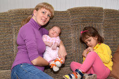 The young woman with two small children sit on a sofa Stock Image