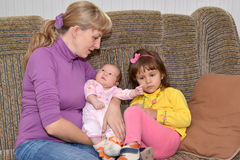 The young woman with two small children sit on a sofa Royalty Free Stock Photos