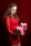 Young woman with two striped gift boxes stares into the camera Stock Photos