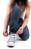 Young woman tying grey gym shoes Royalty Free Stock Photography