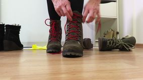 Young woman tying her boots. In brown color on the floor at home stock video
