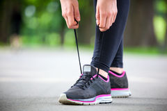 Young woman tying her laces before a run. Stock Photos