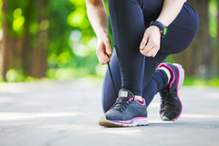 Young woman tying her laces before a run. Stock Images