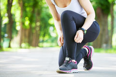 Young woman tying her laces before a run. Royalty Free Stock Images