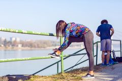 Woman tying jogging shoes. Running outdoors on a sunny day royalty free stock photos