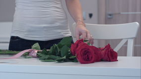 Young woman tying a ribbon bow on red rose bouquet stock video