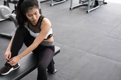 Young woman tying shoelace in fitness center. female athlete pre Stock Photo