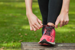 Young woman tying the shoelaces of her running shoes Stock Photography