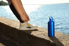 Young woman tying shoelaces near bottle. Of water at riverside on sunny day royalty free stock image