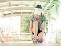 Young woman tying shoelaces. Prepare for start running. royalty free stock image