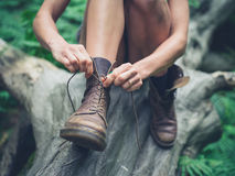 Young woman tyoing her boots in forest Stock Photography