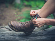Young woman tyoing her boots in forest Royalty Free Stock Images