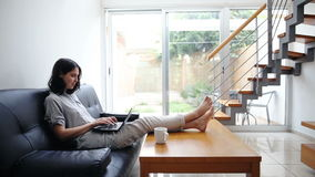 Young woman typing on laptop at cozy home. Pretty young woman typing on laptop at modern cozy home stock footage