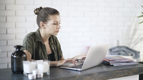Young woman typing at laptop in office. Side view of a beautiful young woman typing at her laptop and using a touchpad in an office. Locked down real time medium stock video