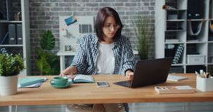 Young woman typing on laptop in office then writing in notebook working