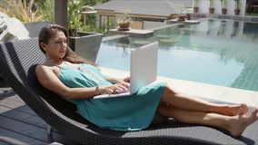 Young woman typing on laptop at poolside stock video footage