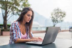 Young woman typing on a laptop studying or working in the park Stock Photo