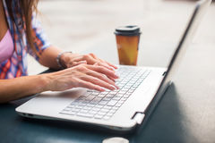 Young woman typing on a laptop studying or working in the park Stock Photography