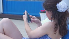 Young woman typing message, chatting on smartphone, sunny beach. Stock footage stock video footage