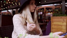 Young woman typing message on phone, sitting in cafe decorated with xmas lights. Young woman wearing hat, typing message on phone, sitting at cafe terrace stock video