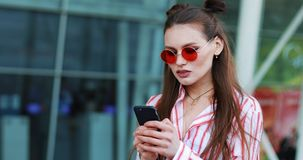 Young woman typing message on the phone standing near a shopping center. Woman in pink sunglasses sunny day blogging stock footage