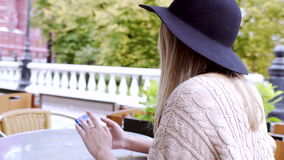 Young woman typing message on phone at the table of moscow cafe stock video footage