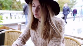 Young woman typing message on phone at the table of moscow cafe. Young woman typing message in phone at the table of moscow outdoor cafe. People walking at the stock video footage