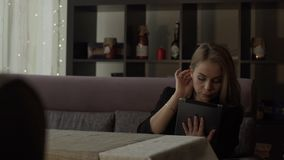 Young woman typing message on screen tablet computer sitting at couch in cafe. Young woman using modern tablet pc on background interior cafe stock video footage